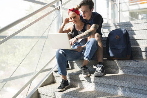Young couple sitting on stairs using laptop - FMOF00307