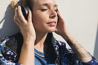 Portrait of young woman with eyes closed listening music with headphones - FMOF00316