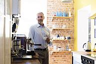 Businessman having coffee break in office kitchen - FKF02449