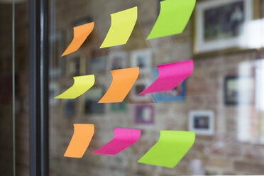 Adhesive notes on glass wall in office - FKF02458