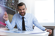 Portrait of confident businessman at desk in creative office - FKF02470