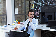 Businessman in creative office taking notes at desk - FKF02473