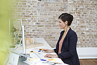 Smiling businesswoman working at desk in office - FKF02497