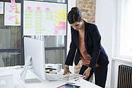 Businesswoman at desk in office looking at printouts - FKF02500