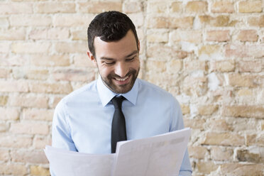 Smiling businessman reading document at brick wall - FKF02506
