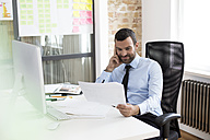 Businessman in office looking at documents at desk - FKF02509