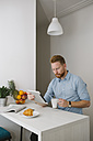 Businessman drinking coffee while using tablet at home - MOMF00197