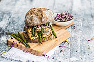 Salmon burger with green asparagus and red cress on chopping board - SARF03344