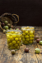 Two jars of preserved gooseberries and gooseberries on wood - LVF06265