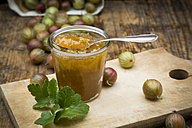 Jar of gooseberry jam and gooseberries on wooden board - LVF06268