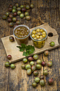 Jar of gooseberry jam, gooseberries and glass of preserved gooseberries on wooden board - LVF06271