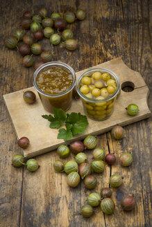 Jar of gooseberry jam, gooseberries and glass of preserved gooseberries on wooden board - LVF06271