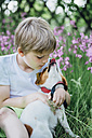Little boy sitting with his dog on meadow in the garden - MJF02131