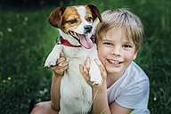 Portrait of happy little boy with his dog on meadow in the garden - MJF02137