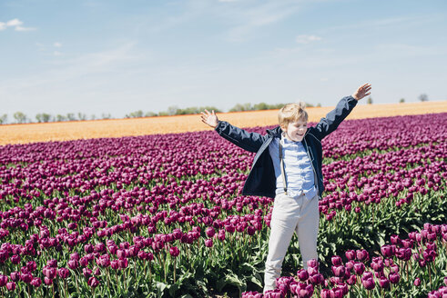 Smiling boy standing on tulip field - MJF02152