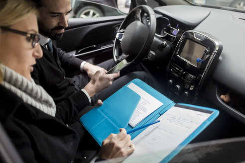 Businessman and businesswoman with documents in car - MAUF01172