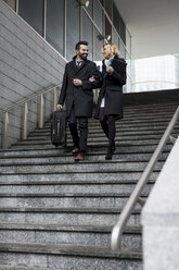 Happy business couple in the city walking down stairs - MAUF01181