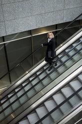 Businesswoman on escalator - MAUF01196