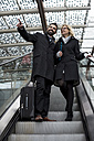 Businessman and businesswoman on escalator - MAUF01202