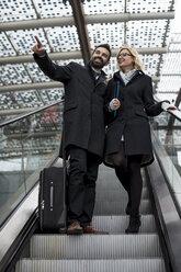 Businessman and businesswoman on escalator - MAUF01202