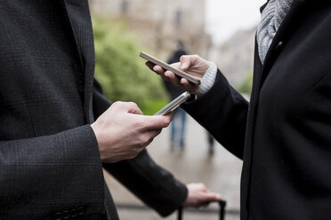 Businessman and businesswoman using cell phones in the city - MAUF01208