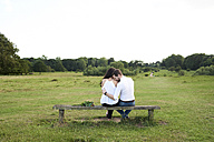 Back view of couple sitting on a bench in a park - IGGF00046