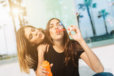 Two happy young women blowing soap bubbles - GIOF02982