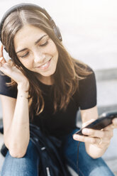 Smiling young woman listening to music outdoors - GIOF02988