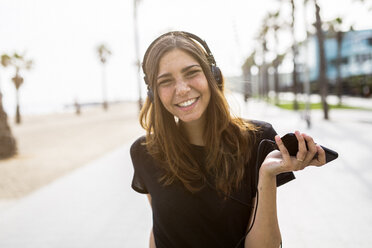 Portrait of happy young woman on boardwalk listening to music - GIOF02991
