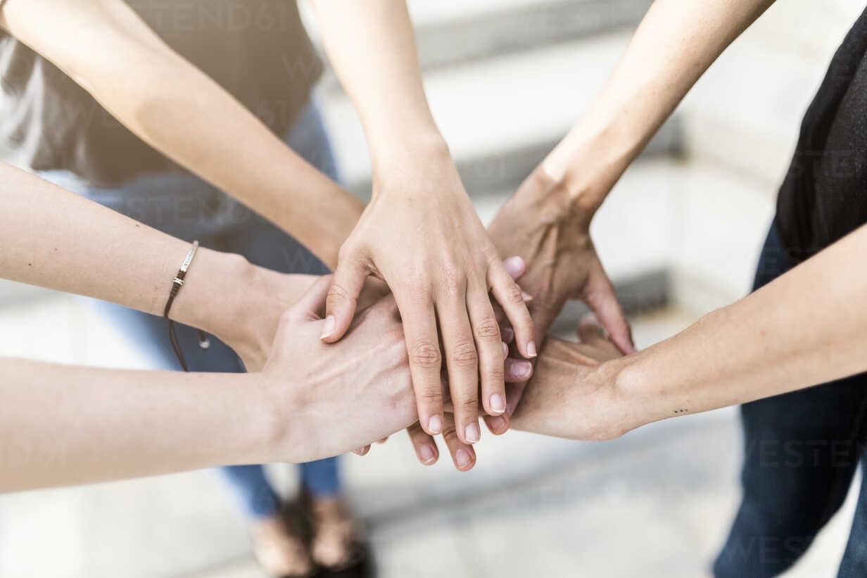Close-up of three women stacking their hands - GIOF02994 - Giorgio Fochesato/Westend61