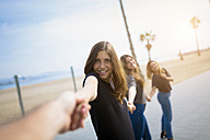 Happy young women holding hands outdoors - GIOF03000