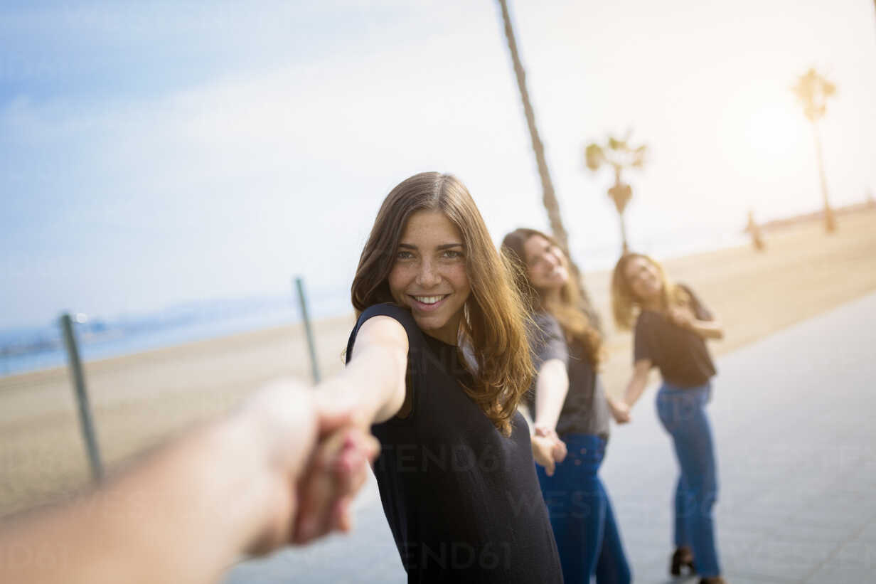Happy young women holding hands outdoors - GIOF03000 - Giorgio Fochesato/Westend61