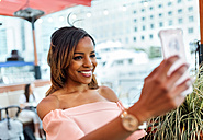Smiling woman taking a selfie in the city - MGOF03454