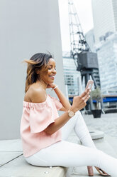 Smiling woman sending messages with her smartphone in the city - MGOF03460