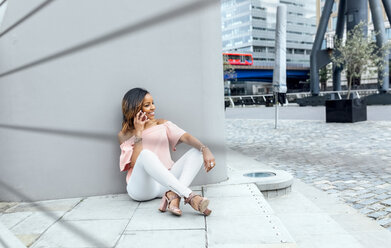 Smiling woman talking on the phone in the city - MGOF03463