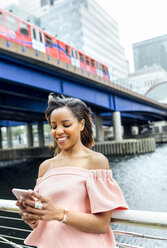 Smiling woman sending messages with her smartphone in the city - MGOF03466