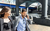 Smiling businessman on the phone and businesswoman in the city - MGOF03469