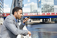 Businessman sending voice messages with his smartphone in the city - MGOF03472