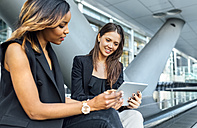 Two businesswomen working with a tablet in the city - MGOF03478