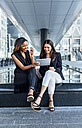 Two businesswomen working with a tablet in the city - MGOF03481