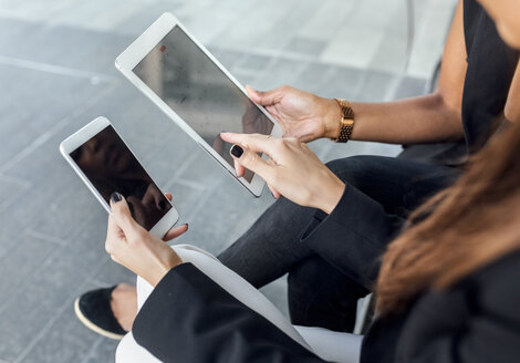 Close-up of two women using smartphone and tablet in the city - MGOF03484