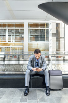 Businessman sending messages with his smartphone in the city - MGOF03487