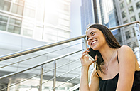 Smiling young woman on the phone in the city - MGOF03499