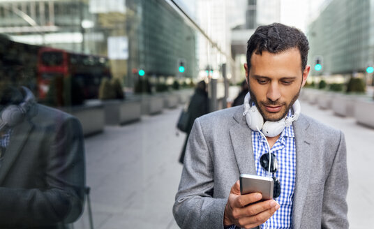 Businessman with headphones and cell phone in the city - MGOF03514