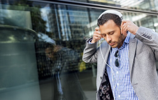 Businessman putting on headphones in the city - MGOF03517