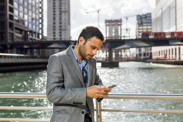 Businessman sending messages with his smartphone in the city - MGOF03523