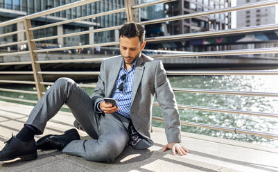 Businessman sitting on a bridge with cell phone in the city - MGOF03526