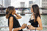 Two women having a coffee break on a bridge in the city - MGOF03529