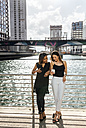 Two women on a bridge sharing a cell phone in the city - MGOF03535