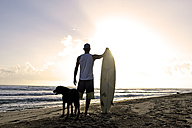 Back view of  man with surfboard and dog watching sunset on the beach - ECPF00007